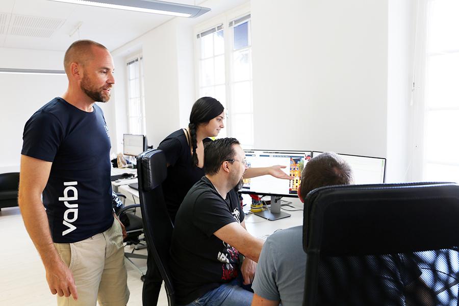 Bild på medarbetare på Varbi som står och tittar på en datorskärm